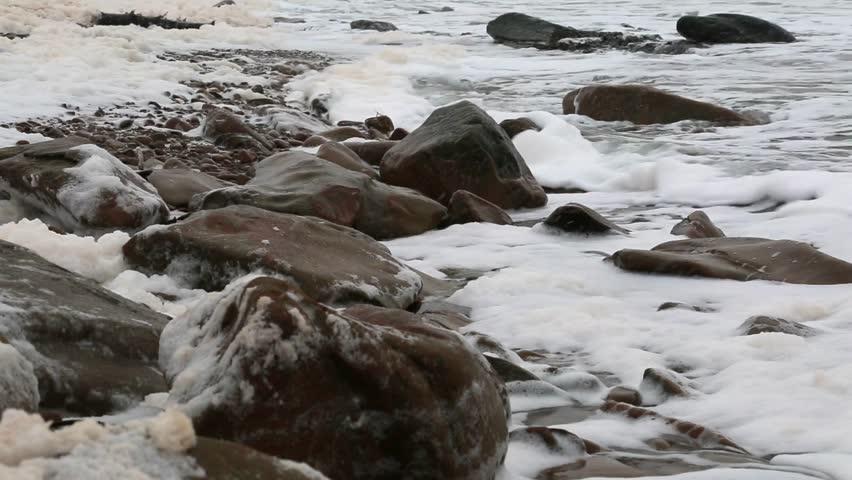 Sea foam on a snow covered winter coastline stock footage video