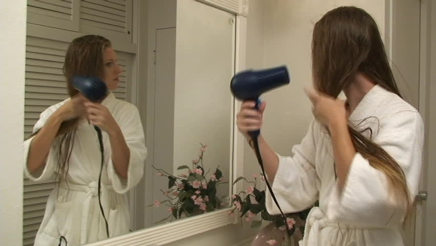 Young woman blow drying her hair in front of the mirror - SD stock footage clip