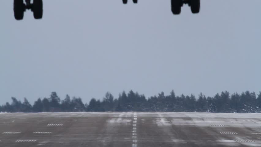 Close-up of an airliner landing on a winter runway