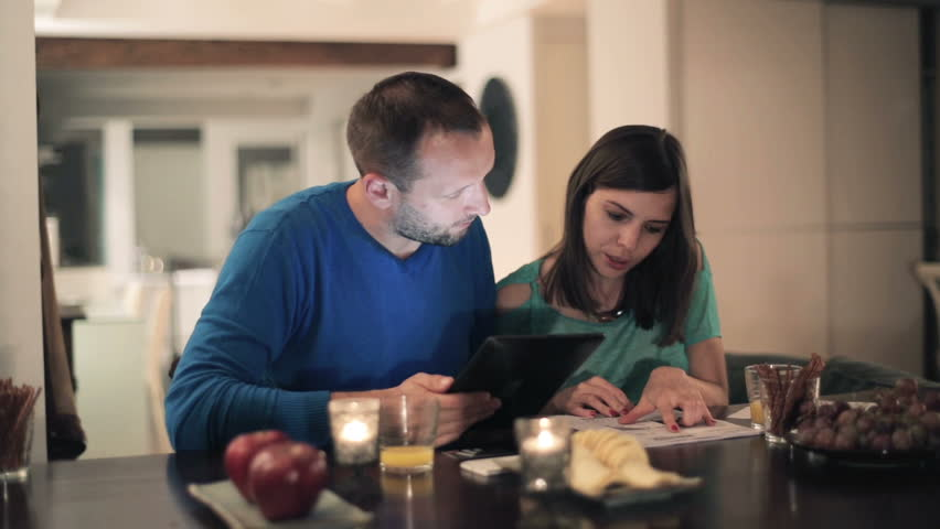 Happy young couple calculating bills by the table at home  - HD stock footage clip