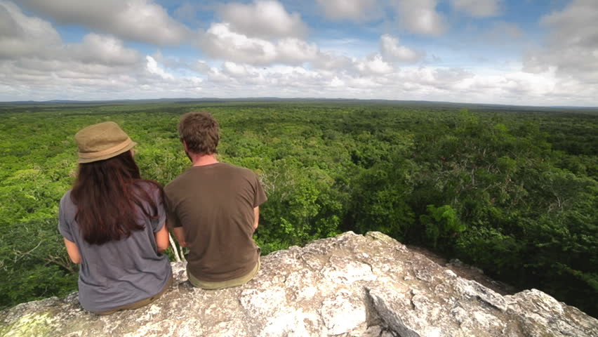 Couple of trekkers on the top of a maya temple enjoying the jungle horizon