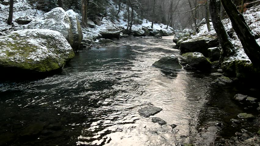 Dark green cold water of mountain stream in winter time between big boulders with snowflakes of first powder snow. - HD stock video clip