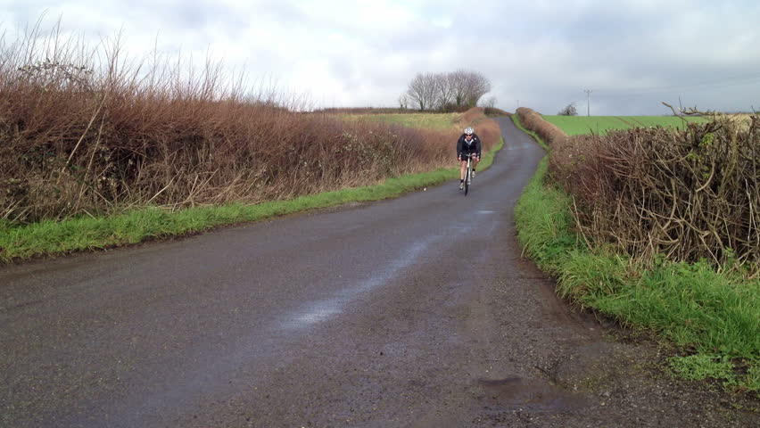 A male road bike racer goes past fast on drop handlebars.