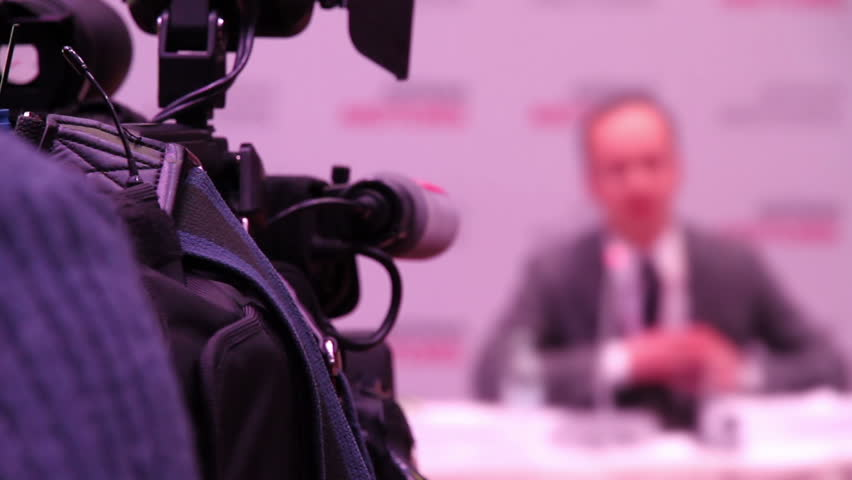 Conference. Television camera focused on a man doing a report on the conference