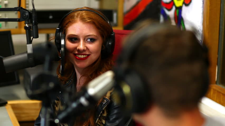 Happy student interviewing someone for radio in the studio in college