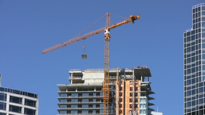 A tall downtown construction crane sweeps to the left carrying heavy cargo on a gorgeous sunny summer day.  - HD stock footage clip