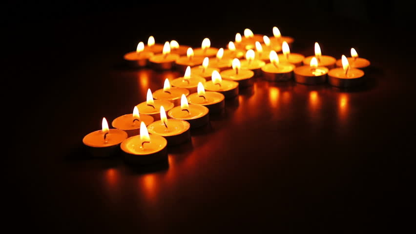 Circular, shallow depth of field, dolly shot of many candles  arranged into a spiritual cross.