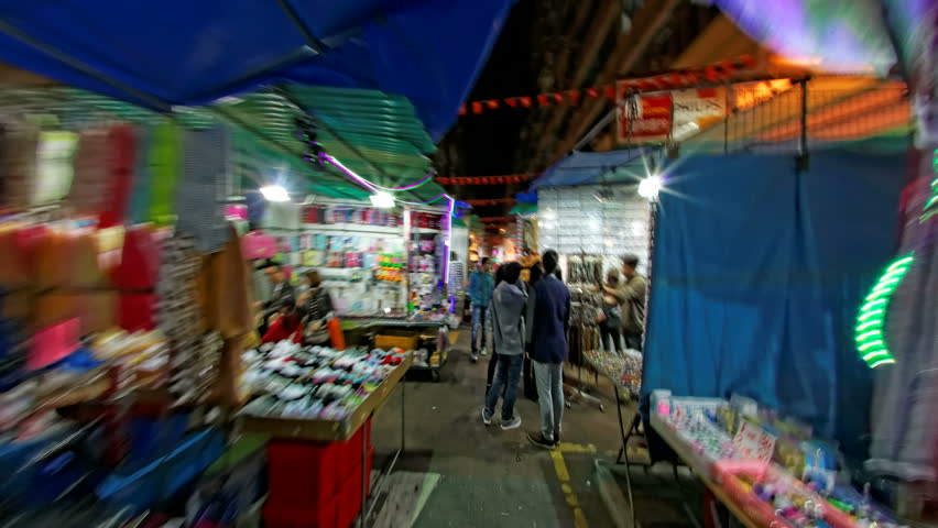 HONG KONG, SAR CHINA - JANUARY 19: World travelers enjoy colorful street night market time lapse  in Mong Kok, buying and selling clothes, toys, electronics and accessories, January 19, 2014. POV