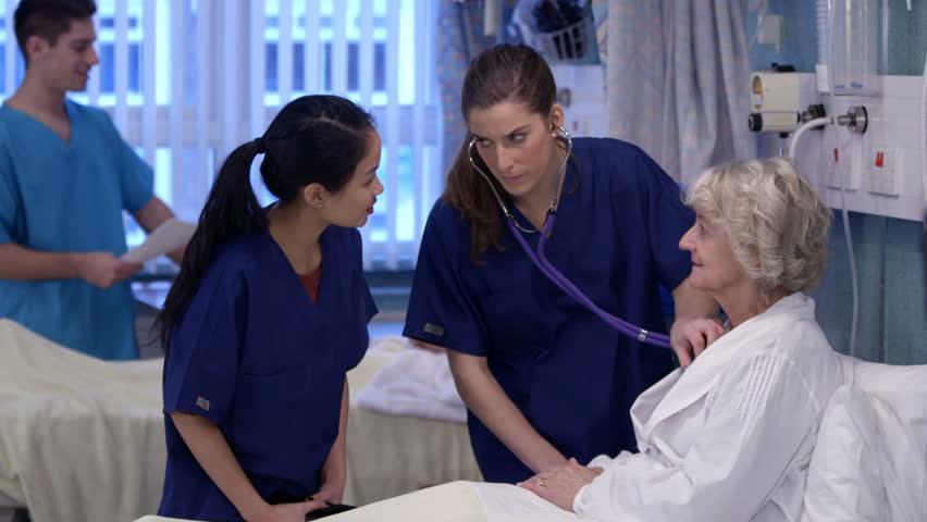 Medical staff working together and taking care of patients on a hospital ward. - HD stock video clip
