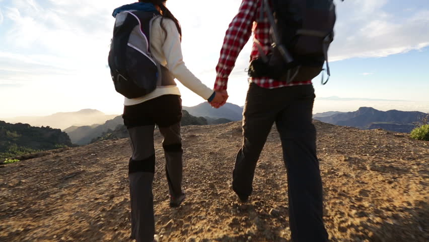 Couple holding hands hiking outdoors at romantic sunset. Hikers man and woman lovers trekking walking with backpacks in trail at sunset in mountains by Roque Nublo, Gran Canaria, Canary Islands, Spain