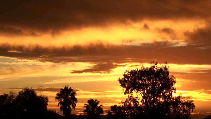 Sunset  time lapse streaks sky with mustard yellow-brown clouds that turn rusty red like autumn leaves. 1920x1080 - HD stock video clip