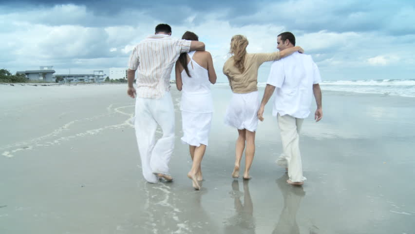 Four attractive young adult friends having fun on the beach together 60 FPS - HD stock video clip