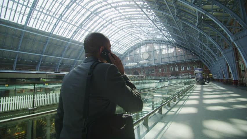 Businessman makes a phone call as he walks through iconic London railway station