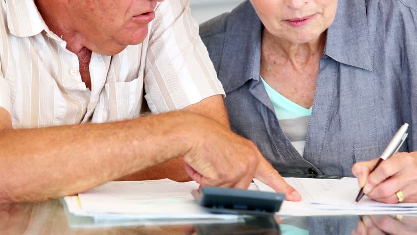 Senior couple paying their bills at home in the kitchen - HD stock footage clip