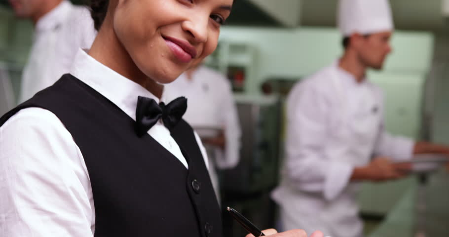 Smiling waitress writing on her notepad in a commercial kitchen