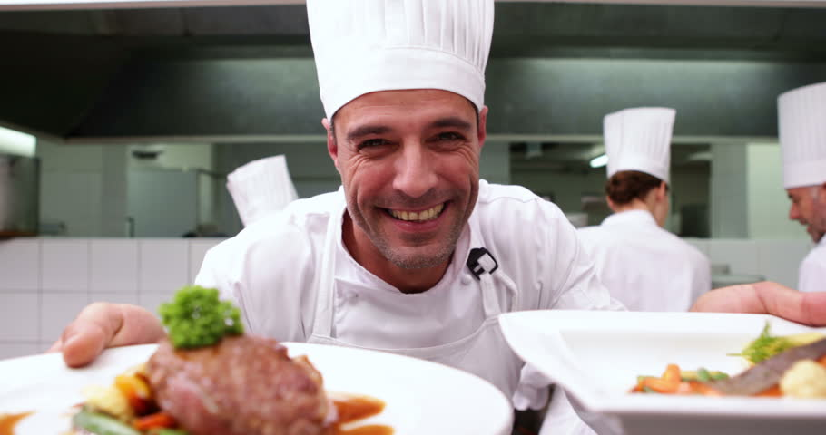 Happy chef showing two dishes to camera in a commercial kitchen