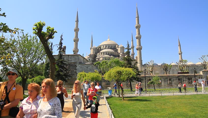 ISTANBUL - MAY 16, 2013: Tourists visit Blue Mosque in Springtime at Sultanahmet Square. Historical Sultanahmet Mosque most famous as Blue Mosque. Tourist group walking in the tour
