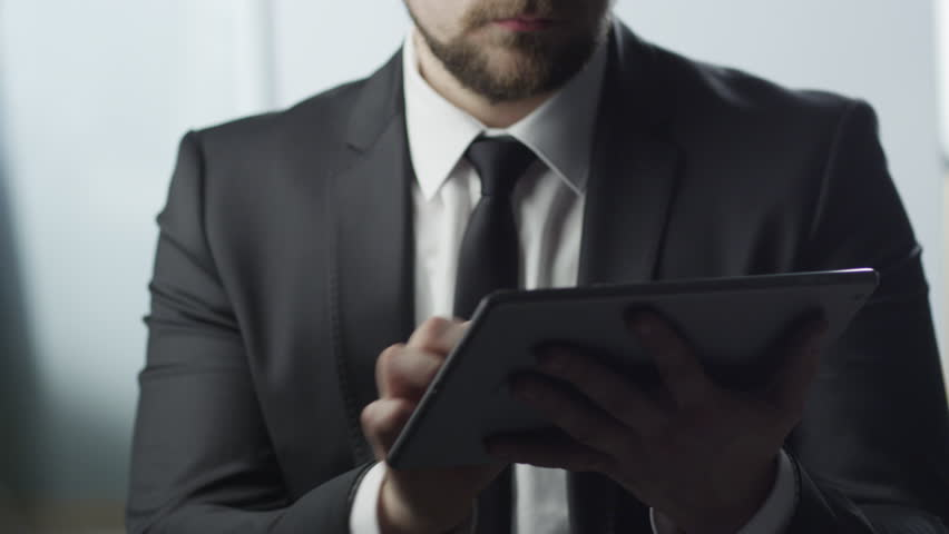 Businessman Using Tablet PC at Work Shot on RED Digital Cinema Camera in 4K (ultra-high definition (UHD)), so you can easily crop, rotate and zoom, without losing quality. ProResHQ