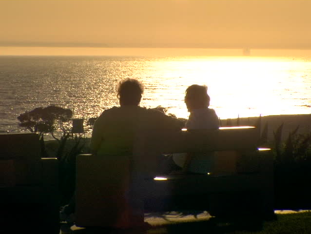 Two silhouetted people watch the sun set in picturesque Orange County. - SD stock footage clip