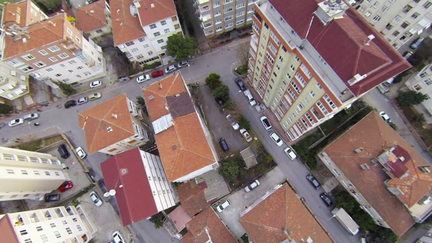 Aerial perspective of apartment buildings over suburban housing. Fly over slide shot from helicopter.