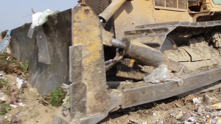 11/35 Bulldozer (tractor) pushes a pile of trash at landfill. Vehicle flattening garbage to waste. Bulldozer moves non biodegradable garbage at the dump. Extreme close up. Footage available in 24fps - HD stock video clip