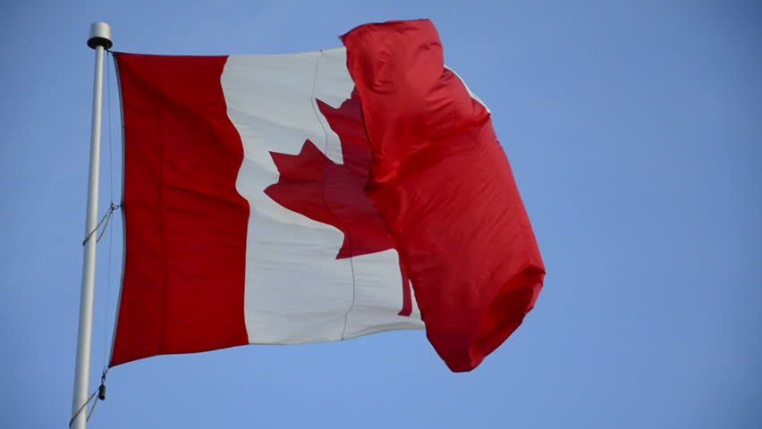 Canadian Flag in a mast waving in a windy day. Red and White, the colors of the Canadian Flag or Union Jack