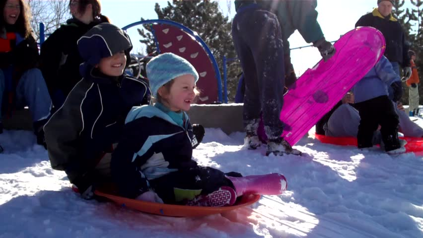 cute little girl slides down a huge snow-covered hill on a sledding saucer - HD stock video clip