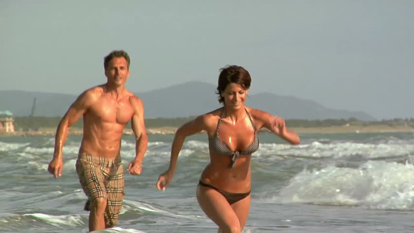 Man and woman running on the beach - HD stock video clip