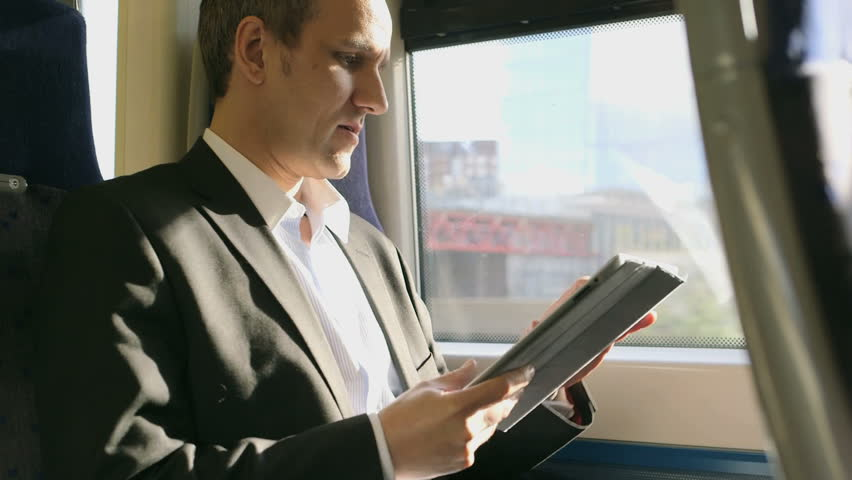 MS Business Man types into his ipad/digital tableton a train