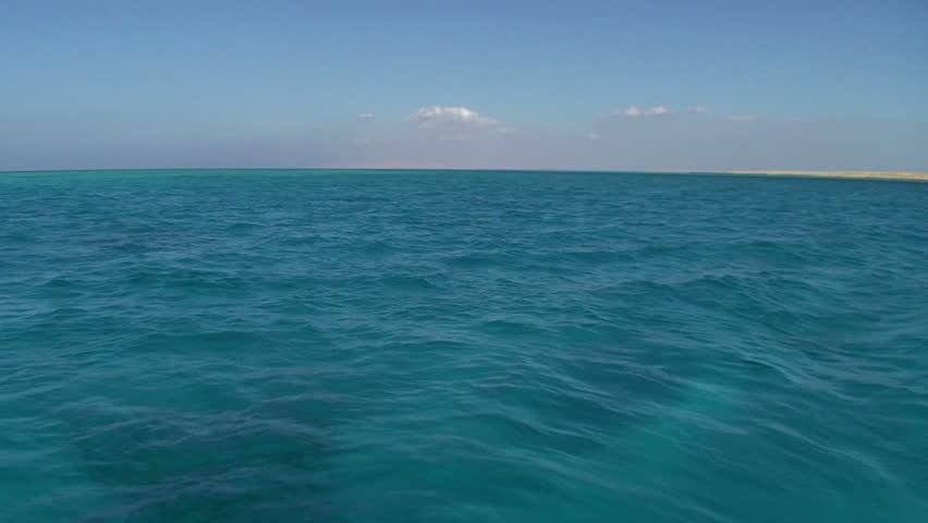 Turquoise water with desert coastline, blue sky and sparse clouds in the background. Gulf of Aquaba, Red Sea, Egypt. - HD stock footage clip