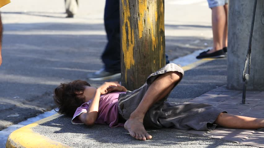 CEBU, PHILIPPINES - MARCH 15, 2014 : Poverty in Philippines, a unidentified boy sleeping on the street. Nearly one of every three Filipino children aged 4 to 10 is underweight
