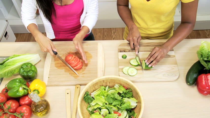 Overhead Multi Ethnic Female Friends Kitchen Fresh Organic Salad - Overhead view healthy female African American Asian Chinese friends working home kitchen preparing fresh organic salad vegetables