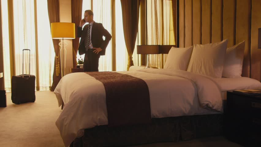 Business travel, people traveling, working in hotel room, manager. Caucasian businessman, man at work, talking on cell phone, mobile telephone. 17of21