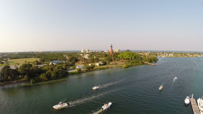 Aerial of a busy Inlet at sunset with the Jupiter Florida Lighthouse.  - HD stock footage clip