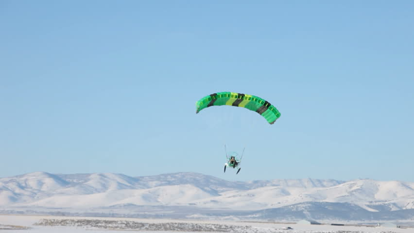Powered parachute flying across a ice and snow covered lake in winter. Central Utah winter recreation and sport. Pilot in aircraft waves. Bright green colored parachute. - HD stock video clip