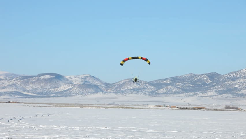 Powered parachute doing a touch and go on ice and snow covered lake in winter. Central Utah winter recreation and sport. Second PPC flying in background. - HD stock video clip