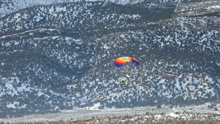 Powered parachute flying low along snow covered mountains in winter. Central Utah winter recreation and sport.  - HD stock footage clip