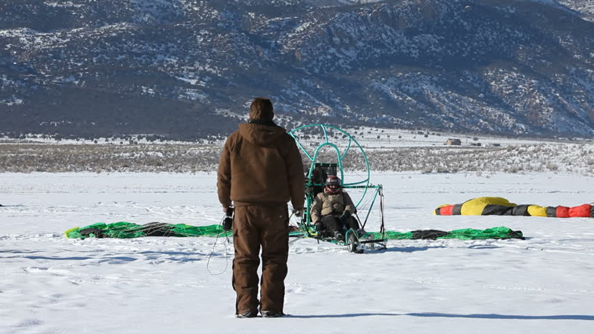 MORONI, UT- CIRCA JAN 2010: Wade Roundy of Moroni watches pilot prepare for flight circa Jan 2010 in Moroni, Utah, USA. Powered parachute start and take off on ice and snow covered lake in winter. - HD stock footage clip