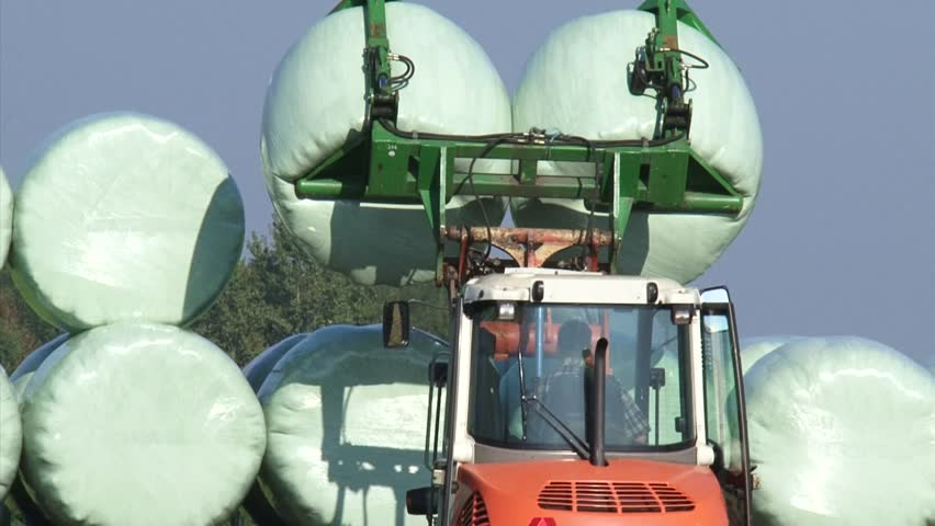 Piling up wrapped hay bales. Round bale silage is a method of preserving forage. It is a combination of hay and silage making. - HD stock footage clip