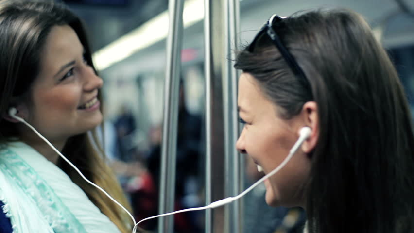 Happy girlfriends listen to music and singing while ride metro train  - HD stock video clip