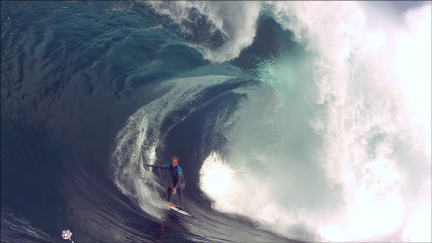 Surfer is towed in to a huge wave, rides it out clean, slow motion part way through after the initial carve