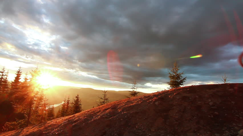 Multiple mountain bikers ride down a trail, amazing sunset in the background landscape