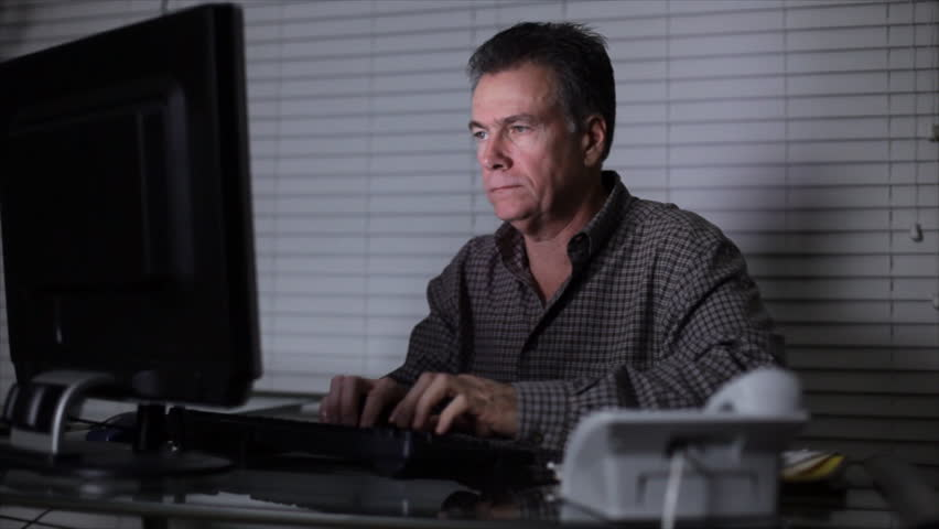 A man at his computer working late at night takes a phone call. - HD stock video clip