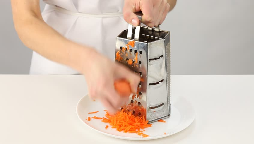 Female cook  grating carrot