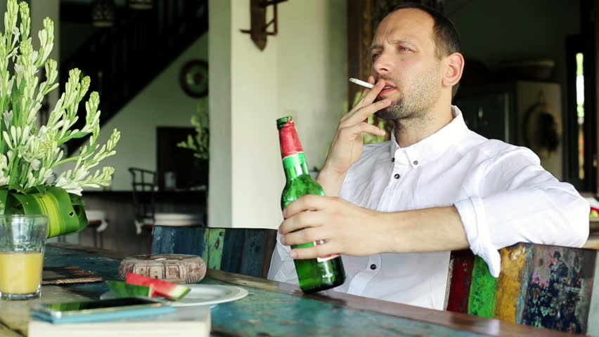 Man smoking cigarette and drinking beer at home  - HD stock footage clip