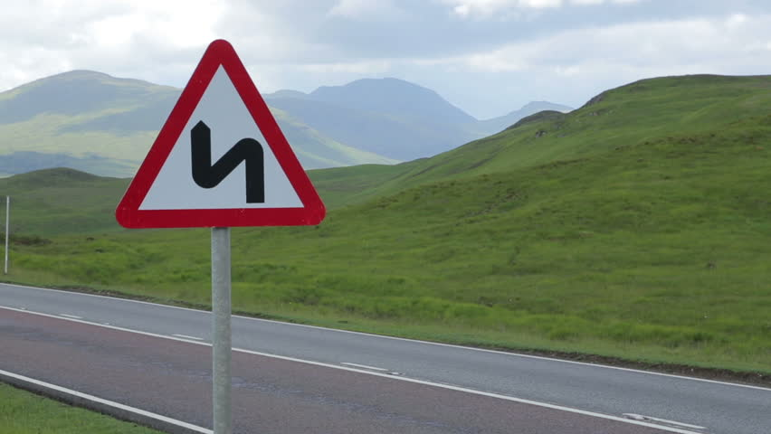 Sharp bends traffic warning as cars drive along road in the countryside in Scotland, UK - HD stock footage clip