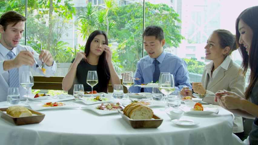 Male female Asian Chinese business partners meeting male Caucasian financial consultant over dinner smart downtown restaurant shot on RED EPIC
