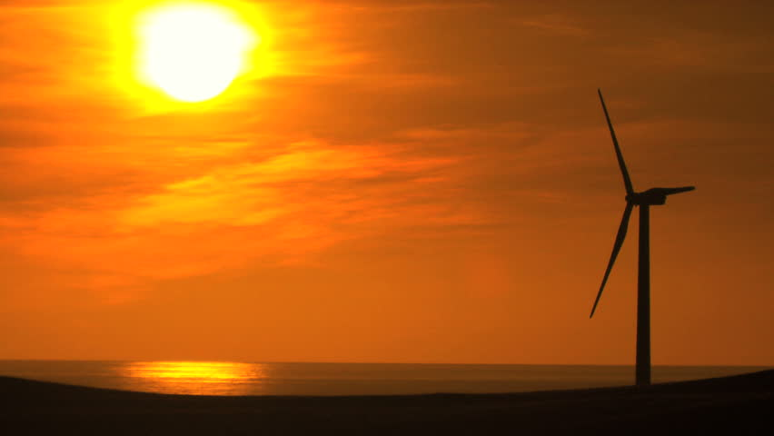 Clean environmental wind turbine in silhouette from full setting sun behind - HD stock video clip