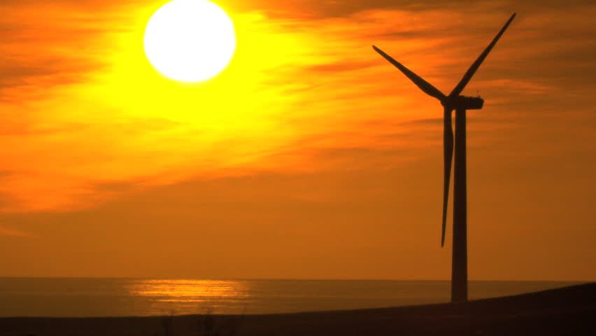 Clean environmental wind turbine in silhouette from full setting sun behind - HD stock footage clip