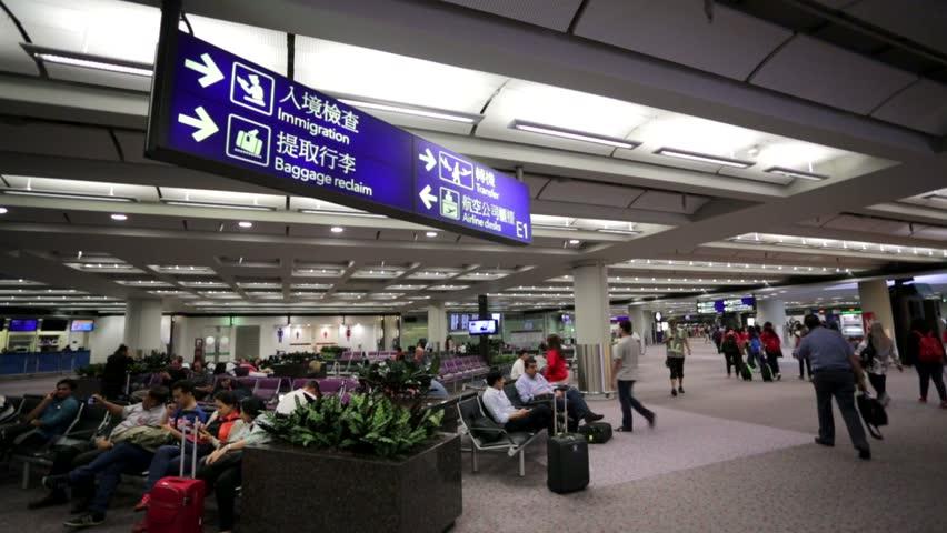 HONG KONG, CHINA - CIRCA JUNE 2014: People in the Hong Kong International Airport. The Hong Kong International Airport is one of the busiest airports in Asia.